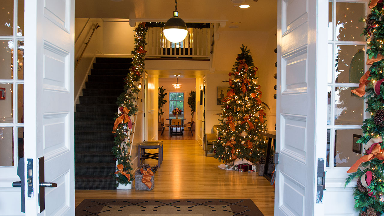 the entrance to inn at the presidio with a christmas tree and presents - The Christmas Inn